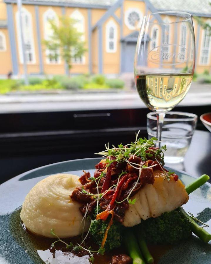 Nærbilde av klippfisk og et glass hvitt vin